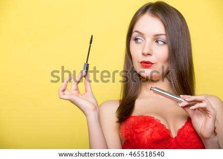 Beautiful sexy girl with mascara. Attractive girl is putting on make-up