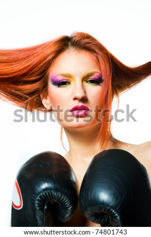 Beautiful sexy girl with multicolored make up wearing boxing gloves on isolated white background