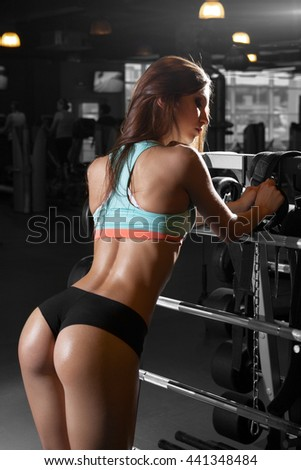 Beautiful sexy girl with perfect buttocks muscles at the gym. The concept of a healthy lifestyle and exercise. Strong woman. Feminism. Fitness brunette model workout in gym. - stock photo