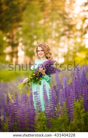 beautiful sexy happy girl with bouquet in the hands of lupine in field at sunset
