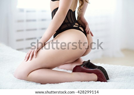 Beautiful sexy lady in elegant black panties and shoes. Close up fashion portrait of model indoors. Beauty woman with attractive body in lace lingerie. Female ass in underwear. Closeup naked girl - stock photo