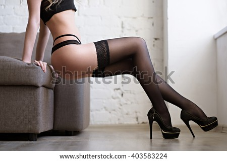 Beautiful sexy lady in elegant black panties and stockings. Close up fashion portrait of model indoors. Beauty woman with attractive body in lace lingerie. Female ass in underwear. Closeup naked girl - stock photo