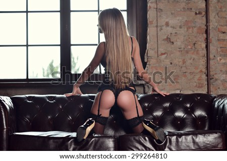 Beautiful sexy lady in elegant black panties and stockings. Portrait of fashion model girl indoors. Beauty blonde woman with attractive buttocks in lace lingerie. Female ass in underwear.  - stock photo