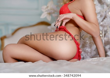 Beautiful sexy lady in elegant panties and bra. Fashion portrait of model girl indoors with christmas tree. Cute woman in lace red lingerie. Female ass in underwear. Naked body - stock photo
