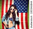 beautiful sexy long haired girl with glass bottle of water and skateboard against american flag sets sunglasses - stock photo