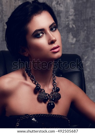 Beautiful sexy makeup elegant woman with bright blue eyes in fashion necklace sitting in armchair on dark background. Closeup portrait