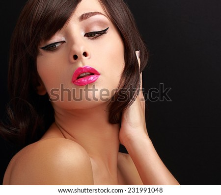 Beautiful sexy makeup woman with pink lipstick and black eyeliner on black background - stock photo