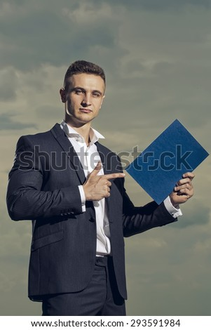Beautiful sexy man in formal suit holding sheet of paper standing on blue sky background copyspace, vertical picture - stock photo
