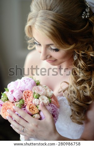 Beautiful sexy model girl in a white wedding dress. Beauty blonde bride without groom. Female portrait with bouquet. Woman with curly hair and lace veil in the hotel. Cute lady indoors