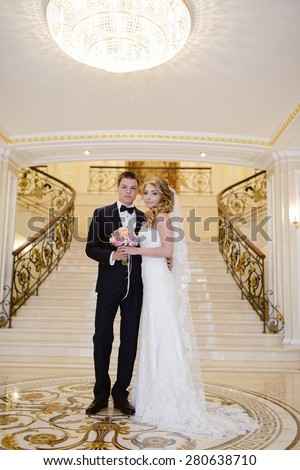 Beautiful sexy model girl in white dress. Wedding couple. Man in suit. Beauty blonde bride with brunette groom. Female and male portrait with bouquet. Woman with lace veil. Cute lady and guy indoors