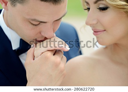 Beautiful sexy model girl. Wedding couple. Man in suit. Beauty blonde bride with brunette groom. Close up female and male portrait. Woman with curly hair and lace veil. Cute lady and guy outdoors