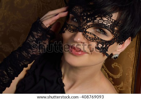 Beautiful, sexy mysterious woman - stranger in the lace mask with short black hair and playful eyes smiling, flirting and drink wine in a wine cellar in the old castle