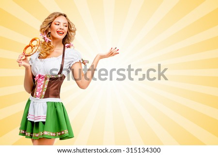 Beautiful sexy Oktoberfest woman wearing a traditional Bavarian dress dirndl posing with a soft salty pretzel on colorful abstract cartoon style background. - stock photo