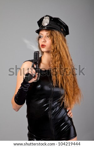 Beautiful sexy police girl with handgun and  isolated on grey background