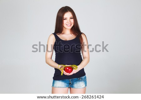 Beautiful sexy pregnant Woman measuring her big pregnant belly with measuring tipe and eating apple. Healthy food. Pregnant Woman tummy. Pregnancy. - stock photo