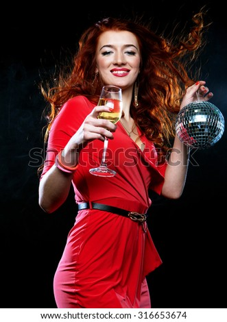 Beautiful sexy redhair woman with a glass of white wine and disco ball - stock photo