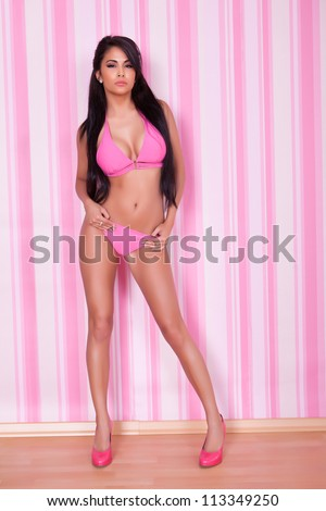Beautiful sexy shapely woman with a sultry look modeling a pink bikini in front of a striped pink studio background - stock photo