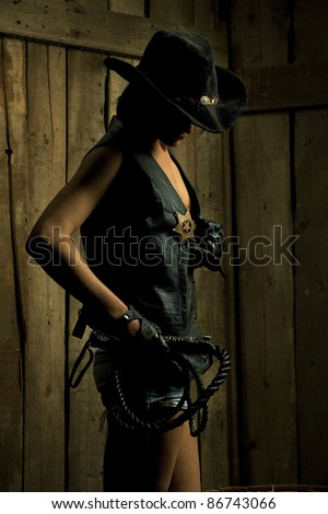 Beautiful sexy sheriff with  Black Leather Flogging Whip against wooden background - stock photo