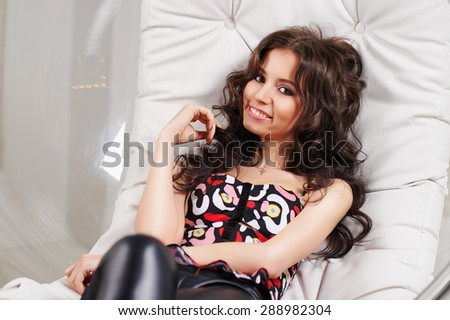 Beautiful sexy slim sporty brunette girl with long curly hair in a t-shirt, black leather leggings and high heels laughs sitting in a glass round chair, hanging from the ceiling on a white background