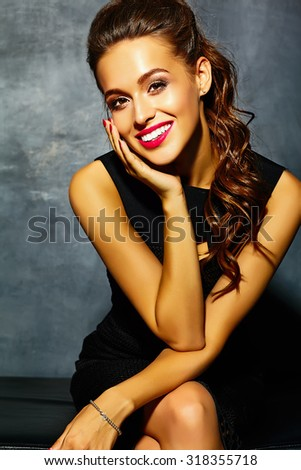 Beautiful  sexy smiling woman model  lady with red lips in black elegant dress sitting on sofa  near gray wall  - stock photo