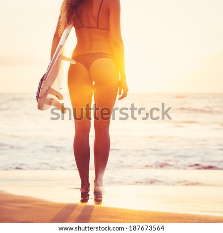 Beautiful sexy surfer girl on the beach at sunset - stock photo