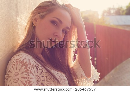 beautiful sexy tender girl near the wall , next to a wooden fence at sunset in the city, volntse hair