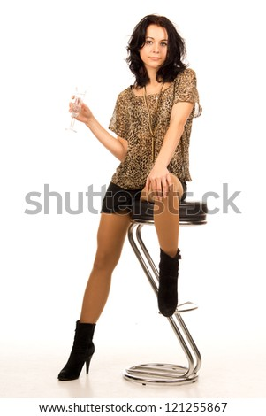 Beautiful sexy trendy young party girl with a glass of champagne posing on a contemporary stool in a miniskirt and high heeled boots