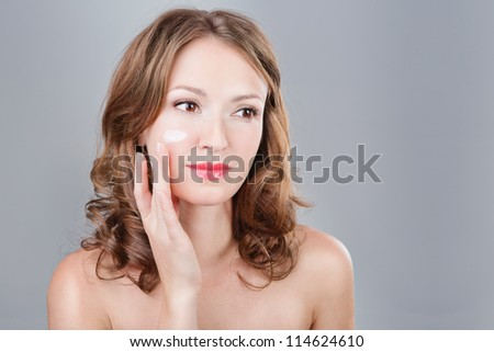 Beautiful sexy woman applying cosmetic cream on face on a cheek. Portrait of young woman applying moisturizer cream on her pretty face. Grey background. Horizontal. - stock photo