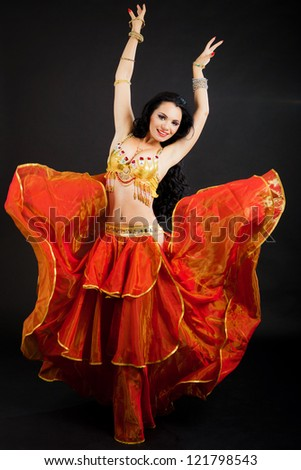 Beautiful sexy woman belly dancer. Arabian oriental professional artist in shining costume with long healthy glossy hair