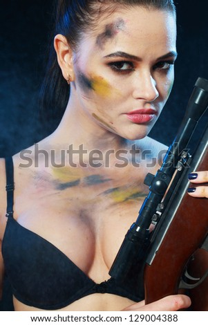Beautiful sexy woman close up holding weapon over dark background - stock photo