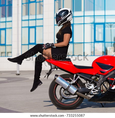 Beautiful sexy woman driver, dressed in black dress, boots, helmet, posing on red motorcycle. Amazing sport portrait. Urban city fashion. Adventure activity hobby.