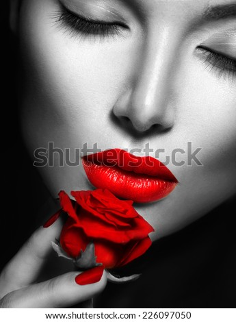 Beautiful Sexy Woman face closeup, makeup with Red Lips, Nails and Rose Flower. Beauty Girl. Passion. Makeup and Manicure. Sensual Mouth. Sexy Red Color Lips. Black and White closeup portrait - stock photo