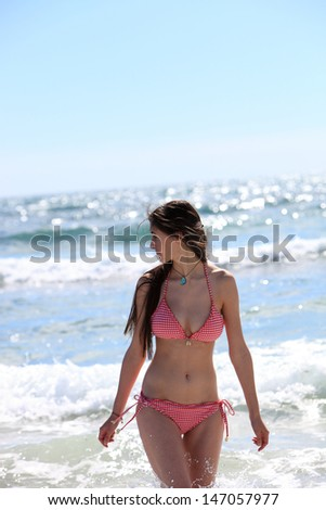 Beautiful sexy woman in a bikini looking back at the ocean as she walks out of the surf towards the camera