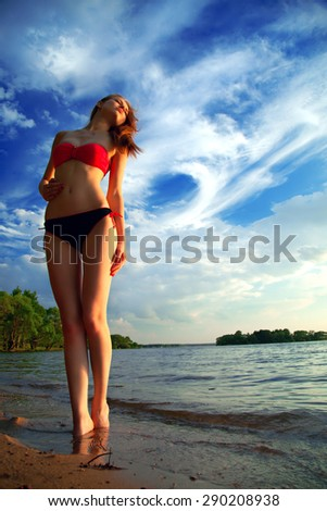 beautiful sexy woman in a swimsuit on the sea coast in summer evening. the trees on the ocean - stock photo