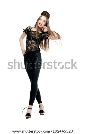 Beautiful sexy woman in black clothes posing on a white background isolated