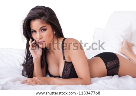 Beautiful sexy woman in black lingerie lying on her stomach on her bed with her feet in the air - stock photo