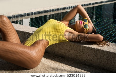 Beautiful sexy woman in fashionable elegant yellow bikini swimsuit and sunglasses lying down and posing with fishnet shadow pattern on her body beside the swimming pool. Summer relax concept