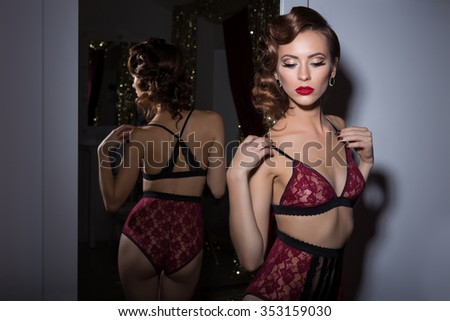 Beautiful sexy woman in lingerie delicate lace retro style 20s with elegant evening hair and makeup stands near the mirror in the dressing room the room - stock photo