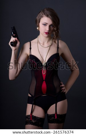 beautiful sexy woman in lingerie posing with gun over grey background - stock photo