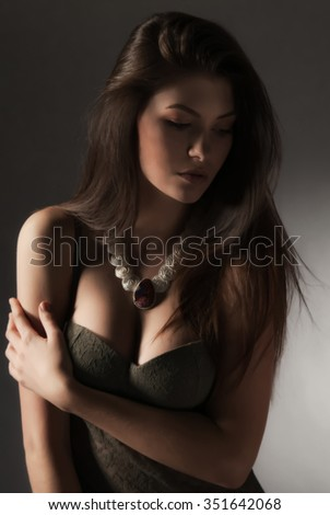 Beautiful sexy woman in lingerie with necklace. Portrait, low key. - stock photo
