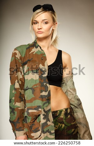 Beautiful sexy woman in military clothes fit army girl on gray