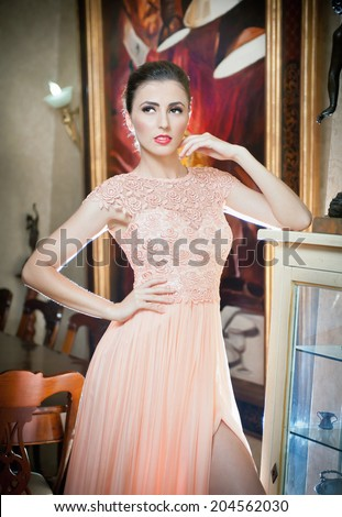 Beautiful sexy woman in pink lace dress in vintage scenery. Portrait of brunette young women with creative hair cut posing in luxury indoor. Attractive young fashionable female in elegant silk dress - stock photo