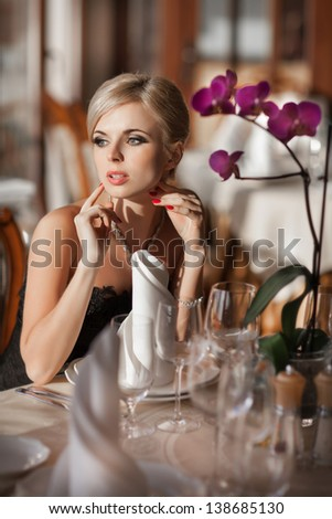 Beautiful sexy woman in restaurant cafe blonde girl rich stylish lady resting at retro villa  hotel with hairstyle makeup jewelry in evening dress. pretty young slim woman in cafe. Happy smiling girl