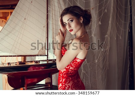 Beautiful sexy woman in restaurant cafe girl rich stylish lady resting at retro villa hotel with hairstyle makeup jewelry in evening dress. Interior and street photography