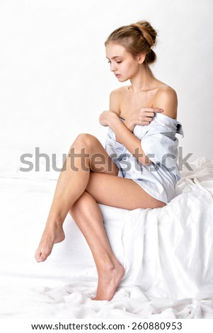 Beautiful sexy woman in shirt sitting on white bed. Studio shooting with white background.