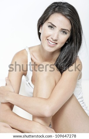 Beautiful sexy woman in white vest top sitting on a white sofa relaxing - stock photo