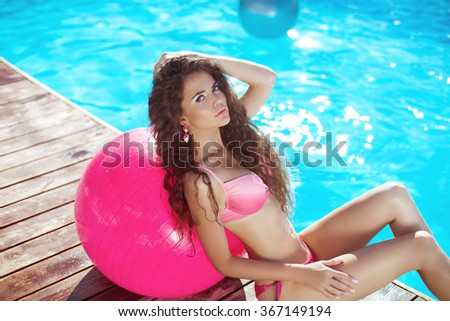Beautiful sexy woman model in pink bikini with pilates fitball posing and tanned by the blue swimming pool on summer vacation. Healthy body care. - stock photo