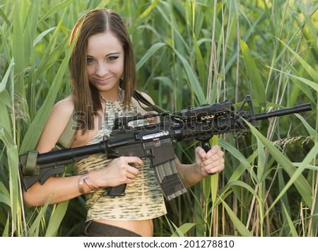 Beautiful sexy woman posing with a gun  - stock photo