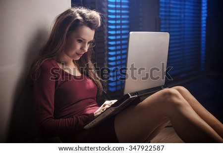 Beautiful sexy woman sitting on floor working on laptop