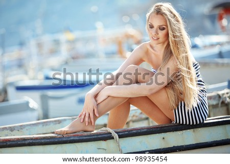 Beautiful sexy woman wearing sailor striped dress posing in boat - stock photo